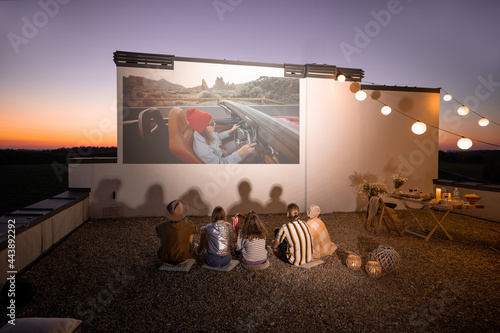 Fotografia Small group of people watching movie on the rooftop terrace at sunset