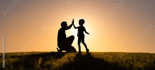 Fotografia, Obraz Father giving son high five. Parent child relationship concept