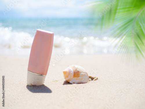 Sunsreen lotion with conch sea shell on sand beach and palm leaves at coast with blur blue sea and blue sky Fototapet