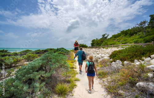Photo Family walking to the beach with sand dunes
