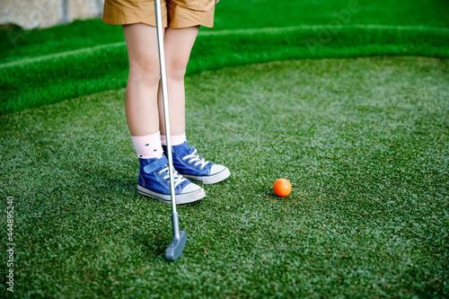 Fotografia Cute preschool girl playing mini golf with family
