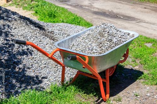 Billede på lærred Wheelbarrow with gravel at the construction site