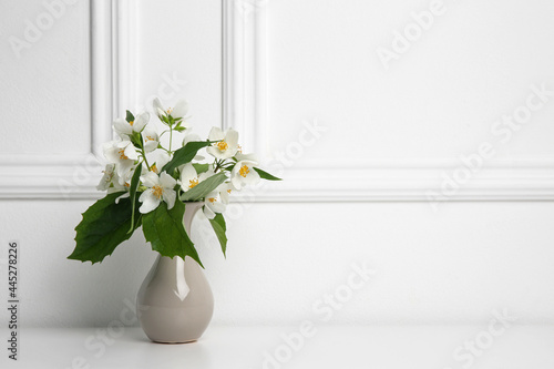 Obraz na plátně Beautiful bouquet with fresh jasmine flowers in vase on white table indoors, spa