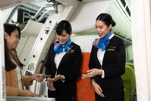 Fotografija Two young beautiful Asian female flight attendants in suit uniform standing at t