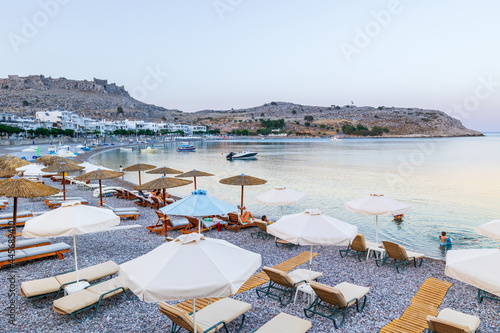 Photographie Umbrellas and sunbeds on an empty evening beach resort - vacation concept on Greece islands in Aegean and Mediterranean seas