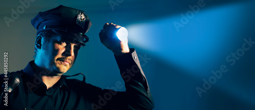 Photo a police officer cop shines a flashlight during an investigation