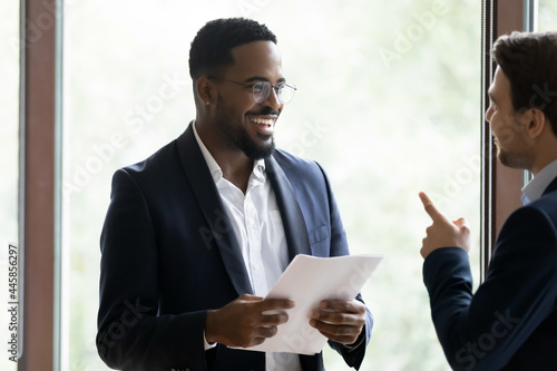 Foto Happy diverse corporate business coworkers standing and chatting at casual meeting at office window