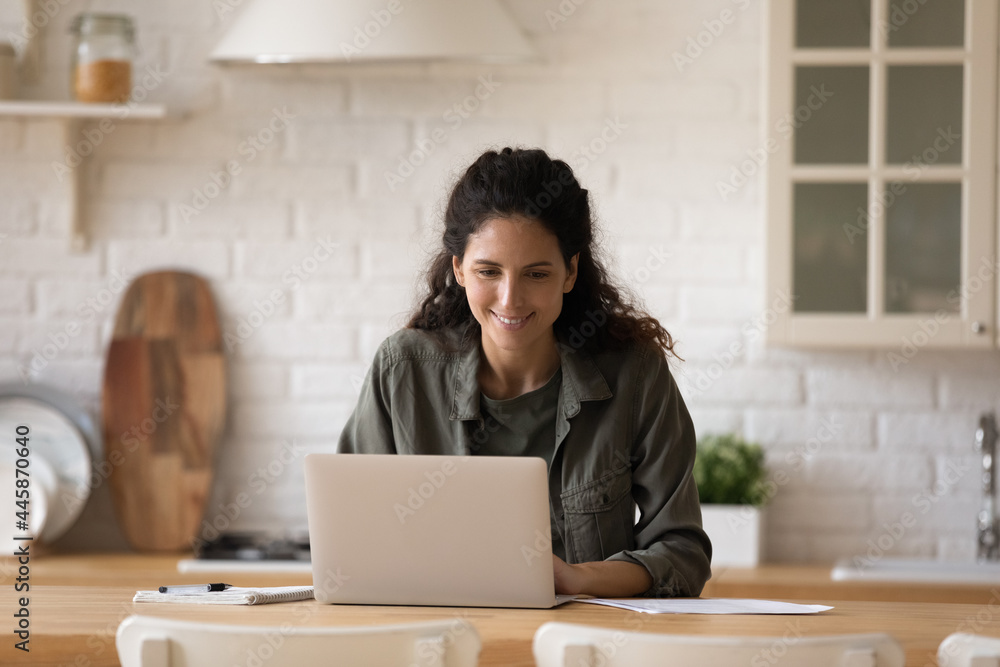 Leinwandbild Motiv - fizkes : Young casual latin lady sit at kitchen table before laptop writing business email managing electronic documents. Busy millennial female expert freelancer working from home on startup project solution