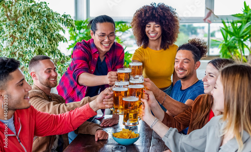 Stampa su Tela diverse group of friends celebrating happy hour making a toast with pint glasses of beers inside a bar restaurant