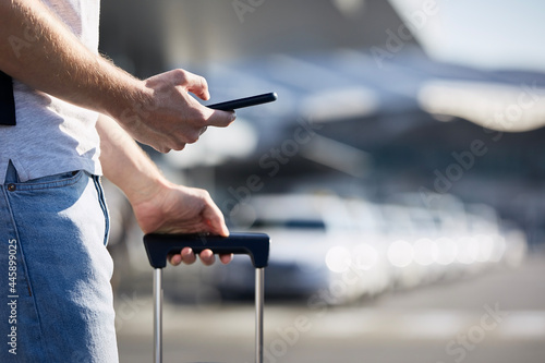 Wallpaper Mural Man holding smartphone and using mobile app against a row of taxi cars