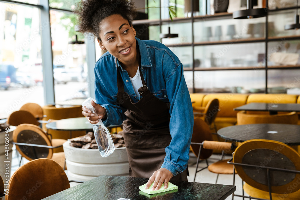 Leinwandbild Motiv - Drobot Dean : Black waitress wearing apron cleaning table while working in cafe