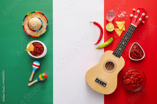 Bowls of tasty salsa sauce and symbols of Mexico on color background