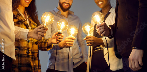 Conceptual banner: happy young multiethnic people holding shining electric light bulbs. Team of coworkers join Edison lightbulbs as metaphor for teamwork and using creative ideas in business community