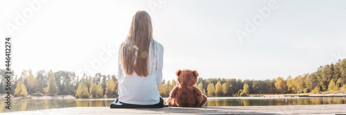 Happy little girl with stuffed toy teddy bear sitting on wooden pier near calm lake on sunny day back view. Banner web site size
