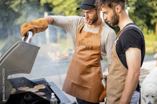 Fotografia, Obraz Two handsome male friends have fun while grilling meat and buns for burgers on g