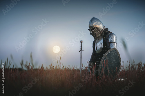 Fototapeta The tired knight in the plate armor kneels among the battlefield with a sword in the moon light