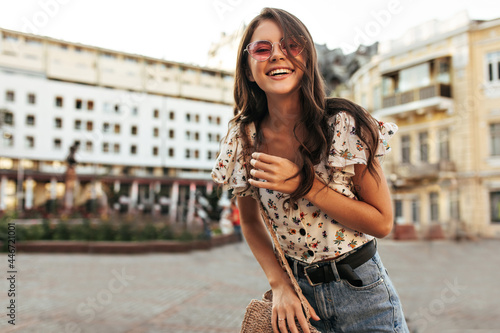 Obraz na plátně Attractive brunette woman in jeans, trendy floral blouse and pink sunglasses smiles sincerely, walks outdoors and looks into camera