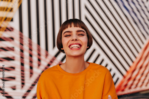 Joyful woman with brunette hair smiling widely on striped background. Trendy short-haired lady in orange sweatshirt posing outdoors..