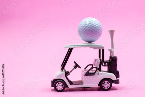 Golf cart with golf ball is on pink background