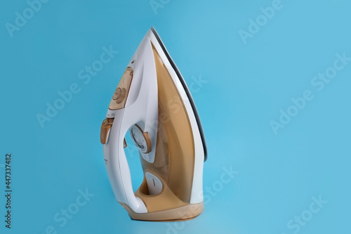 Fotografie, Obraz Studio close up shot of white and gold cordless steam iron isolated on blue background with a lot of copy space for text
