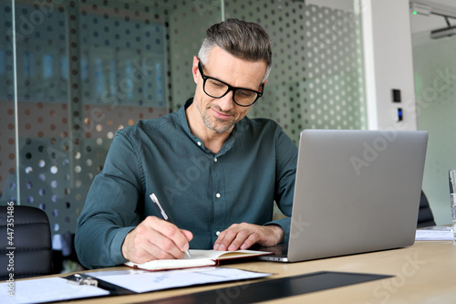 Happy mature executive ceo manager using laptop writing notes in notebook at workplace. Smiling middle aged business man working in office analyzing financial data doing research.
