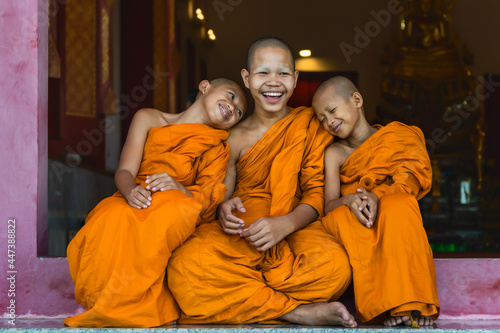 Fotografie, Tablou buddhist novice monks smiling and sitting together at temple gate