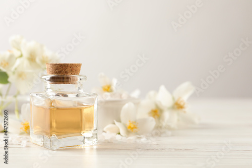 Fotografie, Obraz Beautiful composition with jasmine essential oil and fresh flowers on white wooden table