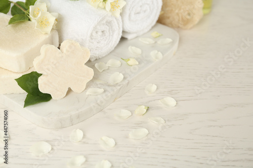 Beautiful jasmine flowers, towels and soap bars on white wooden table
