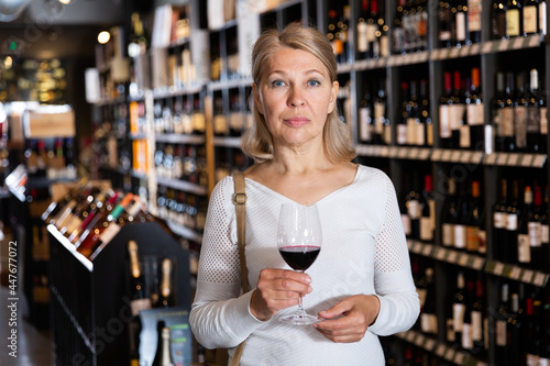 Photo Portrait of mature woman tasting red wine while visiting winehouse in search of bottle of good wine