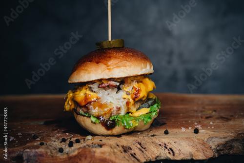 Obraz na plátně Chicken burger with sauerkraut, pickles and mustard on wooden board