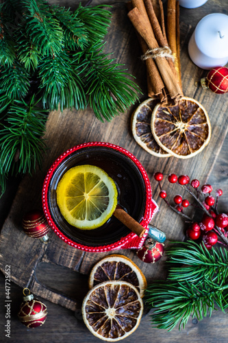 Cup of tea with lemon next to a wrapped christmas gift, decorations and ornaments
