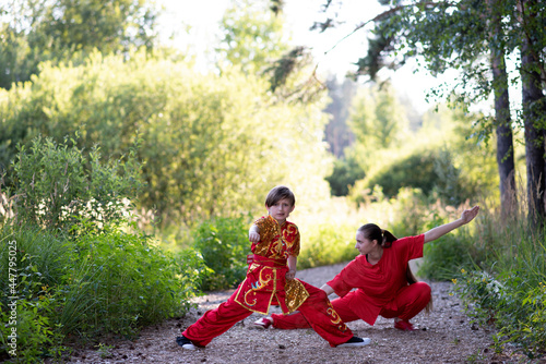 Fotografia teenager girl with little boy in red sports wushu uniform are training in the pa