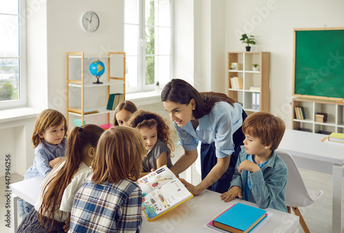 Young friendly caucasian female teacher in the classroom with a book in her hands teaches young students. Modern elementary school students stand around a desk and listen intently to the teacher.