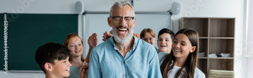 Fotografie, Obraz excited middle aged teacher laughing with closed eyes near happy multicultural p