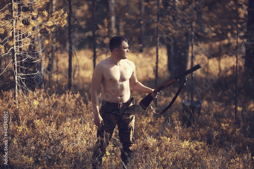 Valokuva hunting man / hunter with a gun hunting in the autumn forest, yellow trees lands