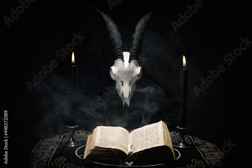 Fototapeta Open old book, goat skull and  black candles on witch table