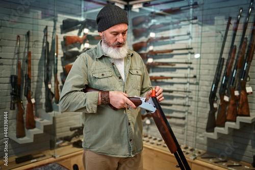 Fotografie, Obraz Bearded male hunter loads rifle in gun store