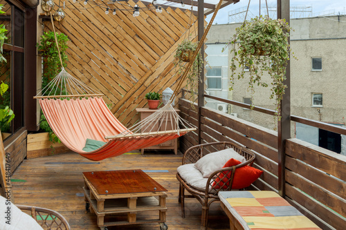 Fotografiet Hammock hangs on wooden terrace with table, flower pots and chairs