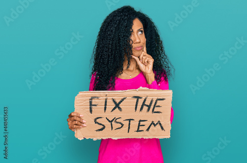 Canvas Print Middle age african american woman holding fix the system banner cardboard seriou