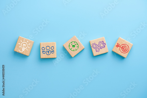 Fotografia Wooden cubes with icons business strategy on blue background, Business process m