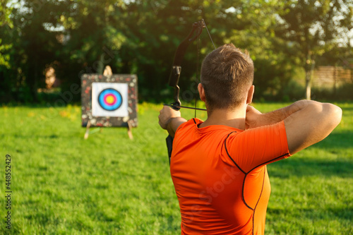 Photographie Man with bow and arrow aiming at archery target in park, back view