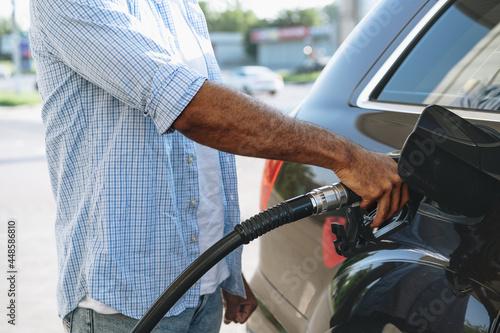 Wallpaper Mural Man filling gasoline fuel in car at gas station
