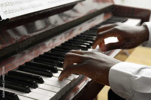 Canvas Print African-American man playing piano, closeup. Talented musician