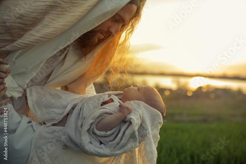 Fotografie, Obraz Saint Joseph holds baby Jesus in his arms.