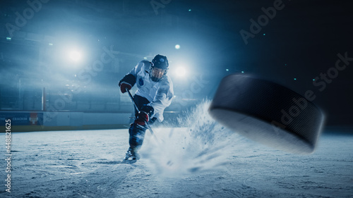 Photo Ice Hockey Rink Arena: Professional Player Shooting the Puck with Hockey Stick