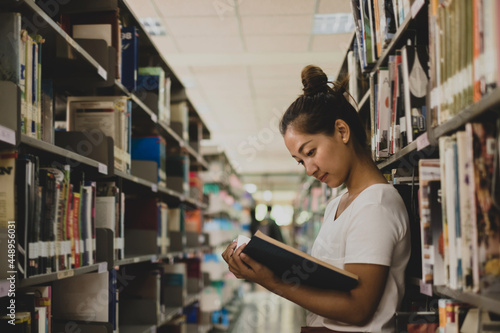 Young Asian women are searching for books and reading books on the tables and aisles of the college libraries to research and develop their academic and education self