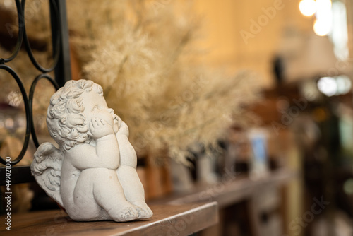 Fotografía A little cherub or angel stone statue is placed on the wooden table