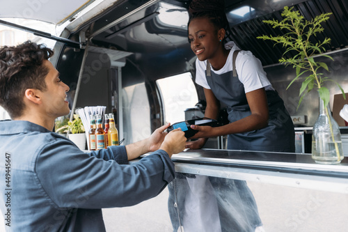 Tela Young man with credit card paying to a saleswoman at a food truck