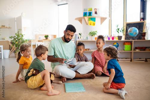 Fototapeta Group of small nursery school children with man teacher sitting on floor indoors in classroom, having lesson