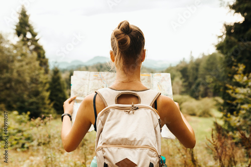 Fotografiet Hiking young woman traveler with backpack checks map to find directions in wilderness area, real explorer